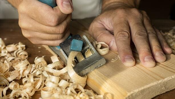 Carpenter Working With Small Saw Making Sawdust