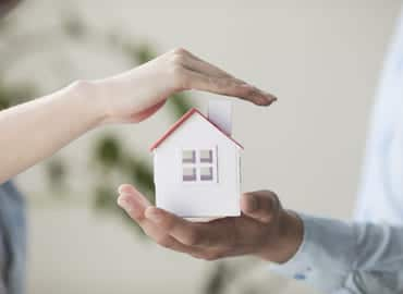 Close Up Hands Protecting Small House Model (1)