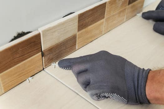 Hands Laying The Tiles