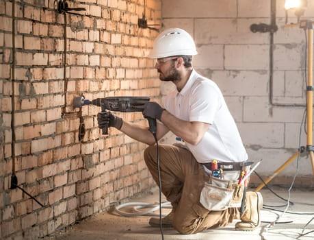 Handyman Uses Jackhammer Installation Professional Worker Construction Site Concept Electrician Handyman