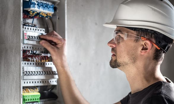Man Electrical Technician Working Switchboard With Fuses Installation Connection Electrical Equipment