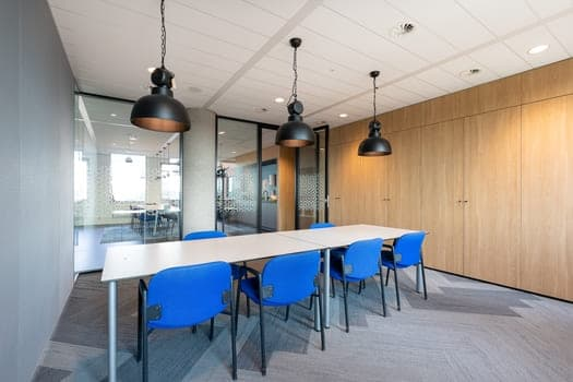Meeting Room Interior Of Modern Office With Long Wooden Table And Chairs Around It
