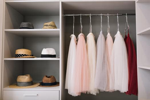 Modern Bright Dressing Room With Shelves Fashionable Hats Beautiful Pink And Red Dresses Hanging In Wardrobe