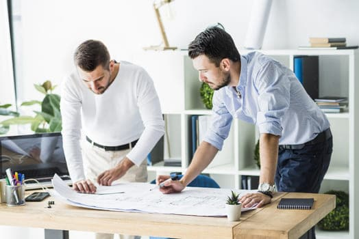 Two Male Architect Working On Blueprint