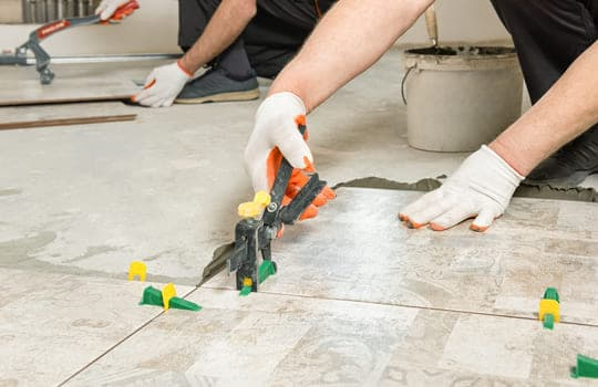 Worker Leveling Ceramic Tile With Wedges Clips