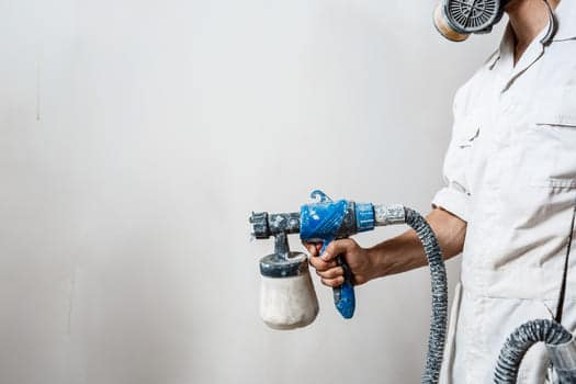 Worker Painting Wall With Spray Gun White Color